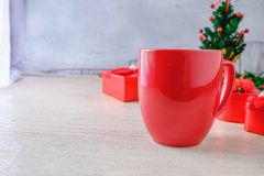 Red Coffee Cup and Red Gift Box with Christmas Tree on White Bac stock images