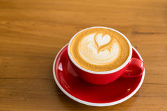 Red Coffee cup with heart shape latte art on wood table at cafe stock images