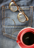 Red coffee cup on jeans background with eyeglasses (relax concept) Stock Photography