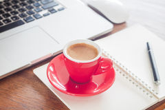 Red coffee cup with notepad and laptop Royalty Free Stock Image