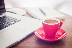 Red coffee cup with notepad and laptop Royalty Free Stock Images
