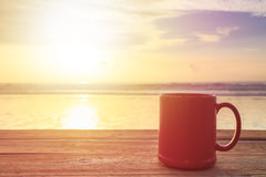 Red Coffee Cup On Wood Table At Sunset Or Sunrise Beach Stock Photo