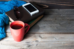 Red coffee cup placed on a wooden table with a smart phone, glasses, books. Copy space Royalty Free Stock Image