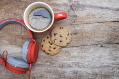 Red coffee cup, Red headphone and chocolate chip cookies on the wooden table. View from above. Coffee with chirstmas concept.  Royalty Free Stock Image
