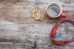 Red coffee cup, Red headphone and chocolate chip cookies on the wooden table. View from above. Coffee with chirstmas concept.  Royalty Free Stock Images