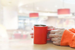 Red coffee cup with smoke in woman hand in coffee shop Royalty Free Stock Images