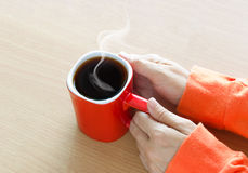 Red coffee cup with smoke in woman hand on wooden table Royalty Free Stock Photo