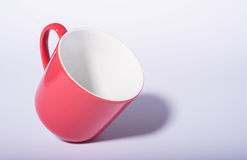 Red coffee cup standing on edge on white background with shadow Royalty Free Stock Photos