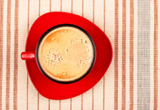 Red coffee cup on striped tablecloth Royalty Free Stock Images