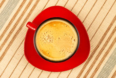 Red coffee cup on striped tablecloth Stock Images