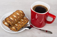 Red coffee cup, stuffed cookies in saucer and spoon Stock Photos