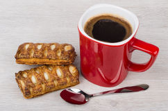 Red coffee cup, stuffed flaky cookies and spoon on table Royalty Free Stock Image
