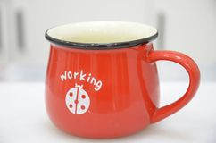 Red coffee cup on the table and in the white background Royalty Free Stock Images
