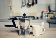 Red coffee cup and  vintage coffeepot on kitchen stove. Background Stock Photography