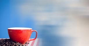 Red coffee cup on red and white table cloth with beans against blue background and blurry sky transi Stock Photos