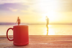 Red coffee cup on wood table at sunset or sunrise beach Stock Photos