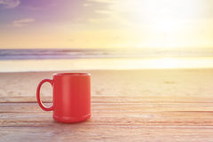 Red coffee cup on wood table at sunset or sunrise beach Royalty Free Stock Photography