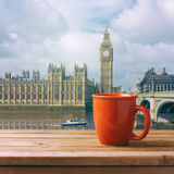 Red coffee cup on wooden table over London Big Ben landmark Royalty Free Stock Image