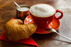 Red coffee mug with croissant and sugar bowl. A tasty composition with warm comforting colors Stock Photos