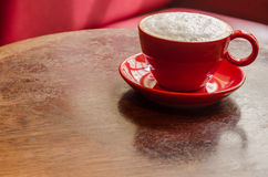 Red coffee mug with frothed milk on an old wooden table. Red mug and plate with coffee and frothed milk on an old wooden table in a cafe Stock Photography