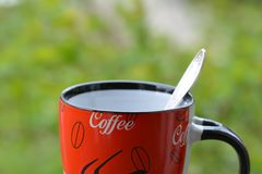 Red coffee mug on green background Stock Image