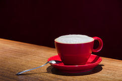 Red coffee mug with a spoon at the bar. A single red mug with coffee and frothed milk with a small spoon in a dark cafe Stock Photos