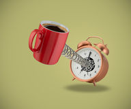 Red coffee mug springing out of alarm clock Stock Images