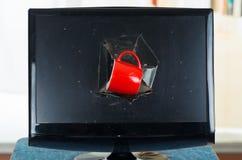 Red coffee mug stuck inside black broken computer Stock Image