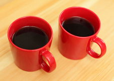 Red coffee mugs. Two red coffee mugs on wooden table stock photo