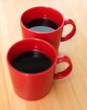 Red coffee mugs. Two red coffee mugs on wooden table royalty free stock photography