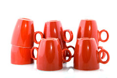Red coffee mugs. Stacked red coffee mugs over white royalty free stock image