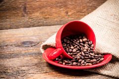 Red coffeecup and plate with spilled coffeebeans. On gunny background Stock Photo