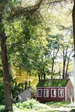Red colonial house in forested setting. A little red house surrounded by fall foliage in colonial Massachusetts stock photo