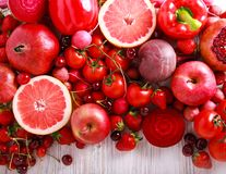 Red color assorted vegetables and fruits. On wooden table royalty free stock image