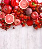 Red color assorted vegetables and fruits. On wooden table stock images