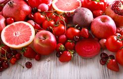 Red color assorted vegetables and fruits. On wooden table royalty free stock photography