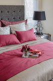 Red color bed and pillows with plant in glass vase on tray. In bedroom Royalty Free Stock Photography