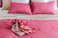 Red color bed and pillows with plant in glass vase on tray. In bedroom Stock Photos