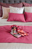Red color bed and pillows with plant in glass vase on tray. In bedroom Royalty Free Stock Photos