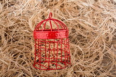 Red color bird cage on straw background Stock Photos