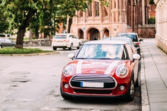 Red Color Car With White Stripes Mini Cooper Parked On Street In Old Part European Town. Stock Photo