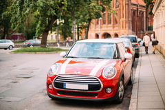 Red Color Car With White Stripes Mini Cooper Parked On Street In Royalty Free Stock Images