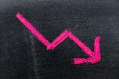 Red color hand drawing chalk in arrow down shape. On black board background Concept of stock decline, down trend of business, economy Stock Photos