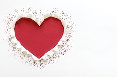 Red color heart love shape with tear white paper. stock photo