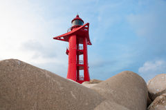 Red color lighthouse in harbor with sky on background Stock Images