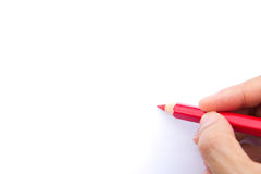 Red color pencil. Hand holds a red color pencil with a white background for text Royalty Free Stock Photo