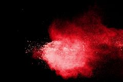 Red color powder explosion on black background.red dust particles splashing. royalty free stock image