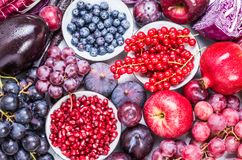 Red color and purple fruits and vegetables background top view. Healthy life diet food concept Royalty Free Stock Photos