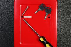 Red cabinet and tool scene. The red color small key box cabinet with screwdriver represent the office supply equipment and hardware concept related idea royalty free stock photo