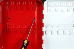 Red cabinet and tool scene. The red color small key box cabinet with screwdriver represent the office supply equipment and hardware concept related idea stock image